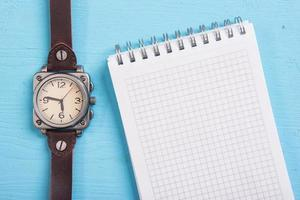 watch and a blank notepad
