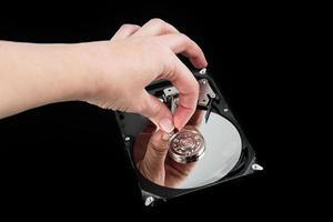 disco duro externo abierto. mano femenina tocando el disco. pérdida de datos foto