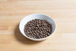 Allspice in a bowl on wood