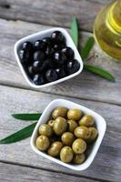 Green and black olives in bowl on grey wooden background photo