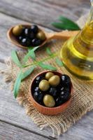 Green and black olives in bowl on grey wooden background