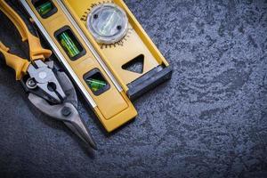 Tin snips construction level on black background