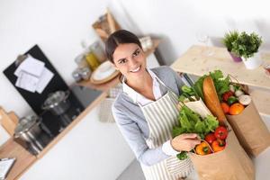 Mujer con bolsas de compras en la cocina de su casa, de pie foto