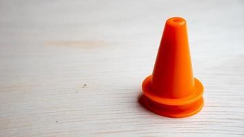Mini conos de seguridad de plástico de múltiples colores sobre superficie de madera