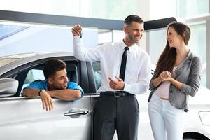 Salesman Giving Key From the New Car to Owners
