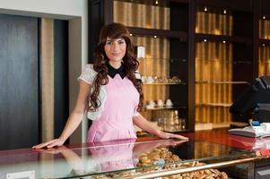 feliz joven vendedor sonriente en una pastelería foto