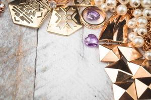 Gold jewelry for elegant women on white wood background