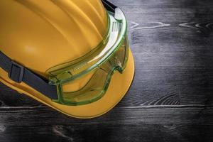 Protective glasses hard hat on wooden board construction concept photo