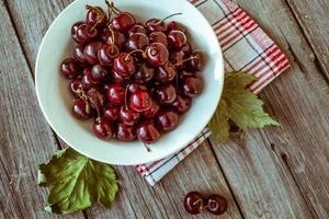 Fresh ripe cherries on a dark wooden board. photo