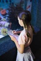 Cute girl looking at fish tank photo