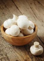 champiñones blancos en un recipiente en la mesa de madera, enfoque selectivo