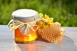 jar of honey piece of honeycomb and wild flowers