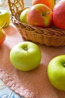 Green and red organic apples in basket