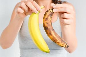Fresh and overripe bananas on woman hand