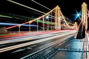 Puente de Chelsea en la noche en Londres con luces de autobús