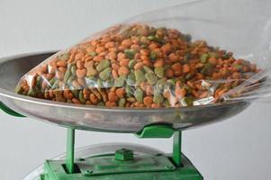 alimento para mascotas en bolsa de plástico en la bandeja de la balanza foto