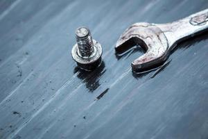 spanner with bolts on top of wooden table