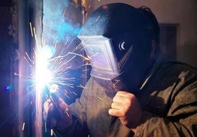 Trabajador con máscara protectora de metal de soldadura foto