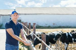 boer werkt op boerderij met melkkoeien
