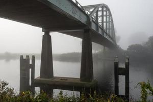 Old iron arch bridge over a small river photo