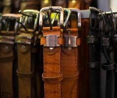 Leather belts collection in the store. photo