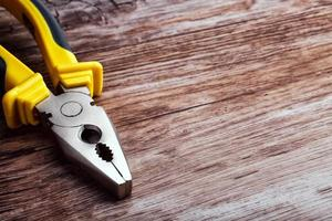 multitool pliers on wooden background photo