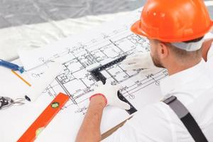 Skillful male engineer is projecting plan of building photo