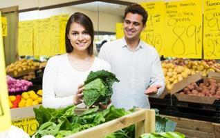 Retrato de joven pareja comprar verduras foto