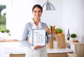 Mujer en la cocina en casa, de pie junto a la mesa con foto