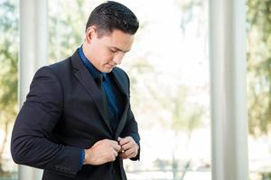 Businessman buttoning his jacket photo