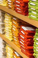 pilas ordenadas de ropa doblada en los estantes de la tienda foto