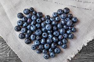 Blueberry heart  lie on a homespun tablecloth on wood
