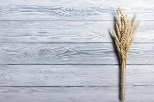 Sheaf of Wheat over Wood Background. Harvest concept. Top view photo