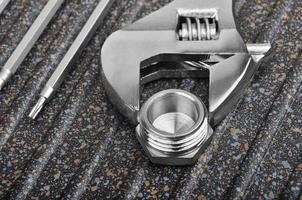 llave inglesa, accesorios de plomería y destornillador foto