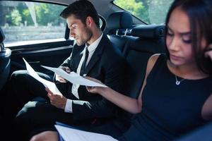 Businesswoman and businessman reading papers in car