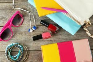Handbag with purse, sunglasses and nail varnish on a table