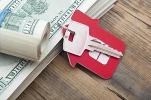 llaves de la casa sobre los billetes de cien dólares foto