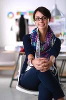 Beautiful fashion designer sitting at the desk in studio photo