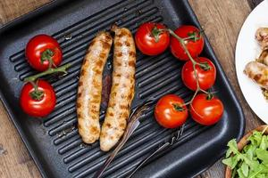 sausages on the grill with tomatoes and arugula