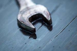 herramienta de llave con gota de rocío sobre la mesa de madera foto