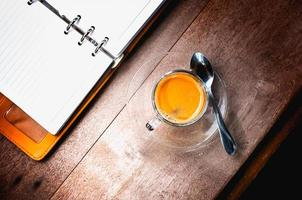 notebook and coffee cup on old wooden background, business conce