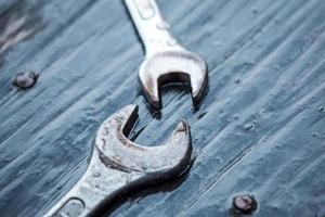 spanner tool with dew drop on top of  wooden table