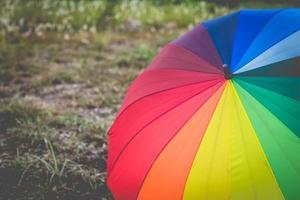 Farewell rainbow umbrella in grass field vintage and retro tone, photo
