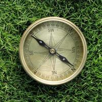 Directional compass in grass photo