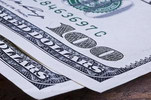 Primer plano de billete de cien dólares en mesa de madera foto