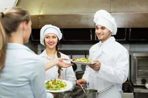 Waitress taking dish from kitchen