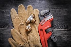 Monkey wrench plumbing fittings leather protective gloves on woo photo