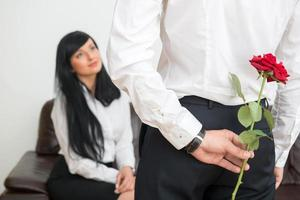 Back view of young businessman  hiding a flower  for his