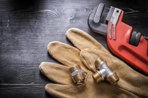 Pipe wrench plumbing fittings safety gloves on wooden board photo