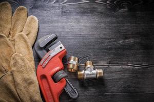 Adjustable wrench plumbing fixtures protective gloves on wooden photo